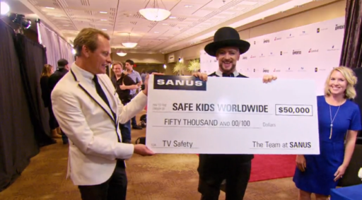 Boy George holding a check